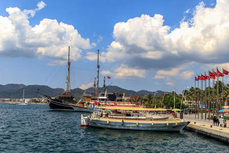 mugla: MUGLA, TURKEY - JUNE 1, 2015 : Sailing ships and people walking around on coastline of Marmaris marina, under cloudy sky.