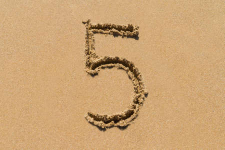The number 5 drawn on sand at the beach, holiday concept background.
