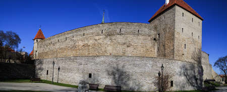 navy blue background: Outside view of ancient fortress walls with towers, exterior view of historical stone Tallinn Walls, on navy blue background. Editorial