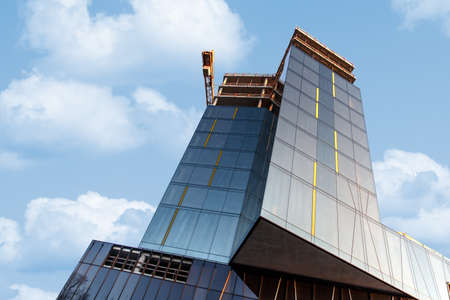 worksite: Bottom view of modern glass-lined building construction in worksite area, on blue cloudy sky background. Editorial