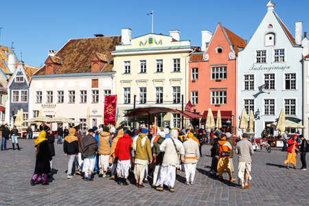 hanging around: TALLINN, ESTONIA - APRIL 25, 2015 : Tourists and locals hanging around square and streets of Tallinn Old Town, on blue sky background.