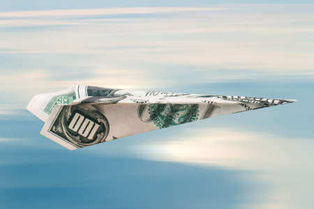 Paper plane with dollar banknote, on blue cloudy sky background. Stock Photo