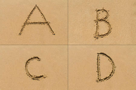 sand: Conceptual set of A B C D letter of the alphabet written on sand with upper case.