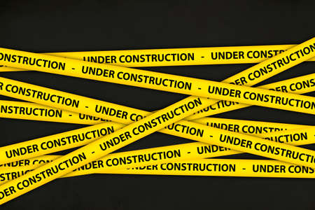 Yellow caution tape strips with text of under construction, on black background.
