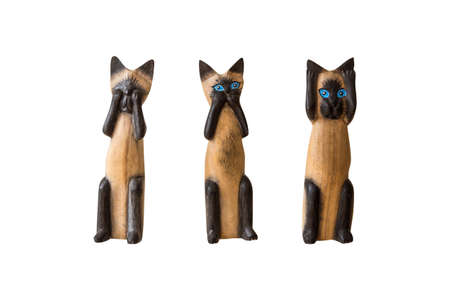 trinkets: Close up front view of brown wooden three siamese cat trinkets, isolated on white background.