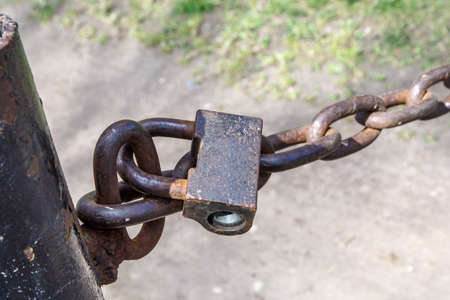 rusty chain: Close up detailed front view of rusty padlock, locked with chain. Stock Photo