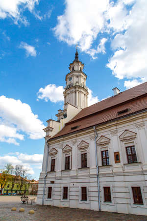 town hall square: Side view of Town Hall building in town hall square of Kaunas old town, Lithuania, built in 16th century, on cloudy blue sky background. Stock Photo