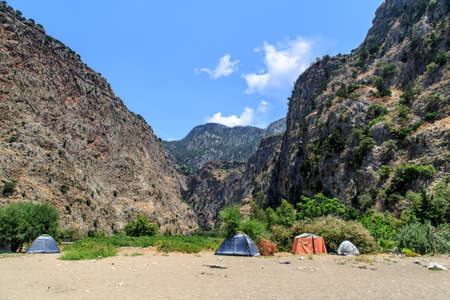 beach butterfly: View of Butterfly Valley with high mountains and camping tents on the beach.