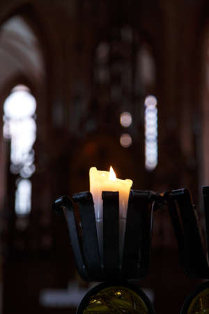 spiritual architecture: Front view of candle in black iron chandelier, burning with a small flame, on dark background.