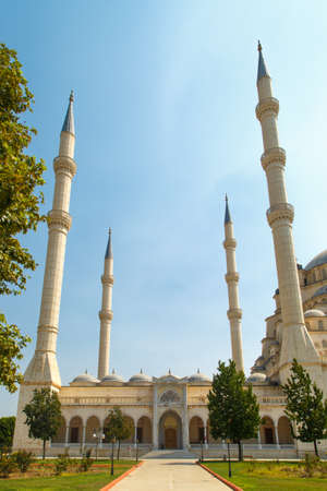 minarets: Exterior front view of Adana Sabanci Mosque, with six minarets, on bright blue sky background.