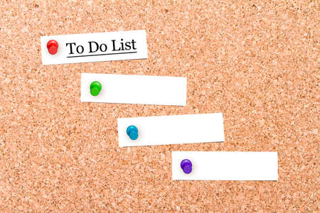 corkboard: Close up front view of illustrative corkboard with to do list text on blank white note cards pinned, on pinboard background.