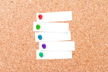 pinned: Close up front view of illustrative corkboard with blank white note cards pinned with colorful pins, on pinboard background.