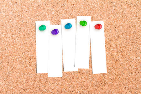 illustrates: Close up front view of illustrative corkboard with blank white note cards pinned with colorful pins, on pinboard background.