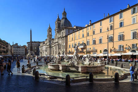 hanging around: ROME, ITALY - SEPTEMBER 26, 2015 : View of historical famous Piazza Navona, with fountain and people hanging around, on bright blue sky background.