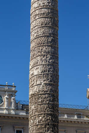 hieroglyphics: Close up detailed view of Column of Marcus Aurelius with historical hieroglyphics at Piazza Colonna, on bright blue sky background.