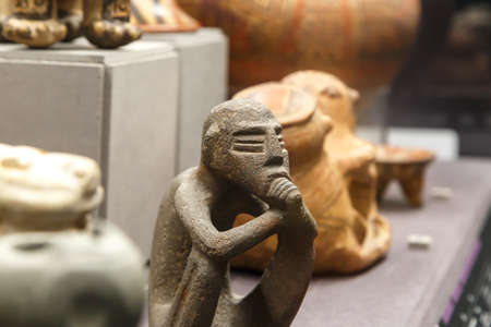 historical events: FLORENCE, ITALY - SEPTEMBER 20, 2015 : Close up detailed view of small basaltic olmec figurine exhibited in Florence Archeology Museum.
