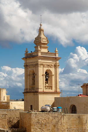 apartment tower old town: View of a historical church in Victoria, Malta with a limestone belltower, on cloudy sky background. Stock Photo