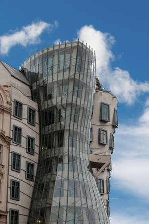dancing house: View of famous glass building with asymmetrical shape Dancing House, on cloudy blue sky background. Editorial