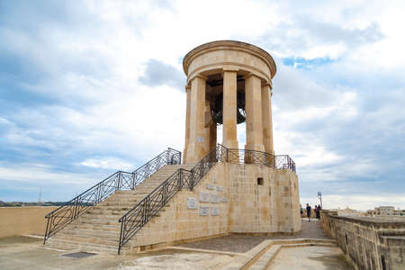 siege: VALLETTA, MALTA - OCTOBER 30, 2015 : View of the bell tower of Siege Bell Memorial in Valletta, Malta, on cloudy blue sky background.