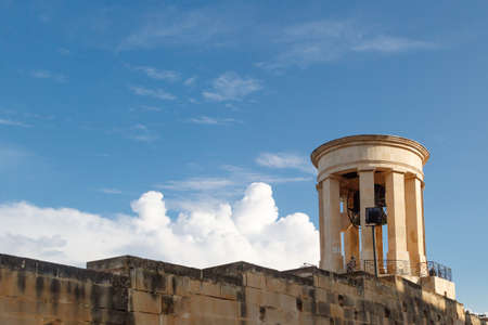 siege: View of the bell tower of Siege Bell Memorial in Valletta, Malta, on cloudy blue sky background.