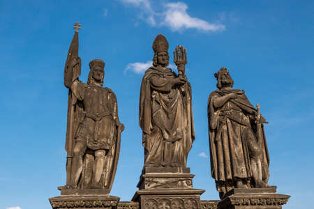 granit: Close up detailed view of historical gothic granit sculptures on Charles Bridge in Prague, on bright blue sky background.