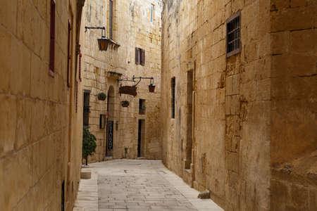 historical buildings: MDINA, MALTA - NOVEMBER 1, 2015 : View of narrow Mdina streets with limestone historical buildings around.