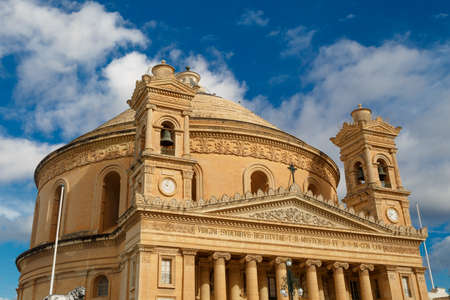 rotunda: MOSTA, MALTA - NOVEMBER 1, 2015 : Exterior view of Rotunda of Malta known as also Mosta Dome, historical and the third biggest church in Europe, on cloudy blue sky background.