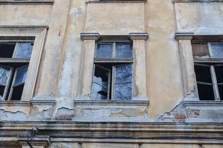 yellow stone: Bottom view of destroyed abondoned yellow stone building with broken windows. Stock Photo