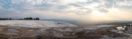 geographical: Panoramic view of Pamukkale Travertines with geographical formations on cloudy sky background at sunset time. Stock Photo