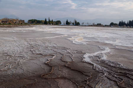geographical: General view of Pamukkale Travertines with geographical formations on cloudy sky background at sunset time.