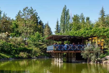 arbour: AYDIN, TURKEY - MAY 1, 2016 : Landscape view of natural park with lake, trees and wooden arbour on bright blue sky background.