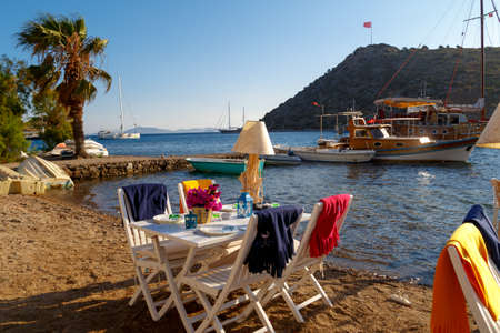 mugla: MUGLA, TURKEY - MAY 28, 2016 : View of restaurant with white tables and chairs along Gumusluk beach. Editorial