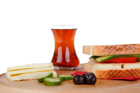 View of a sandwich with cheese, tomato and cucumber with black tea, isolated on white background.