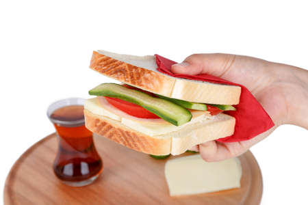 View of a sandwich with cheese, tomato and cucumber holding on hand, isolated on white background. Stock Photo