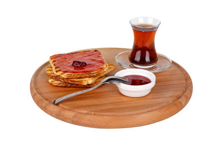 Side view of burnt toasted bread with jam and tea on wooden board, isolated on white background. Stock Photo