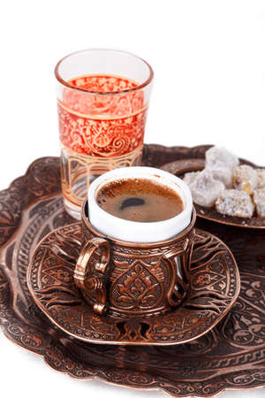 Traditional cup of Turkish coffee with foam, water glass and Turkish delights, top view, isolated on white background.