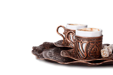 Traditional cup of Turkish coffee with foam and Turkish delights, isolated on white background.