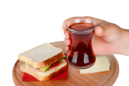 Close up front view of glass of black tea holding on hand, with a sandwich on a wooden plate, isolated on white background. Stock Photo