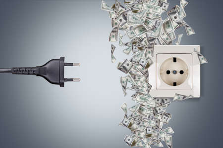 Close up detailed view of white jack and black plug with dollar banknotes around on grey background. Stock Photo