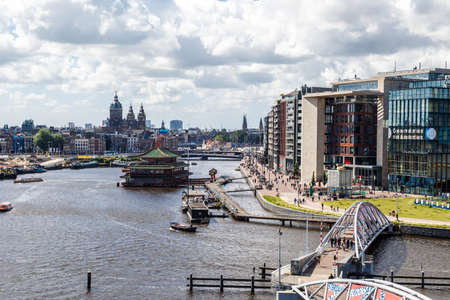 AMSTERDAM, NETHERLANDS - JULY 2, 2016 : Cityscape view from Nemo Science Museum on cloudy sky background. Nemo Science and Technology Museum is a popular attraction in Amsterdam designed by Renzo Piano. Editorial