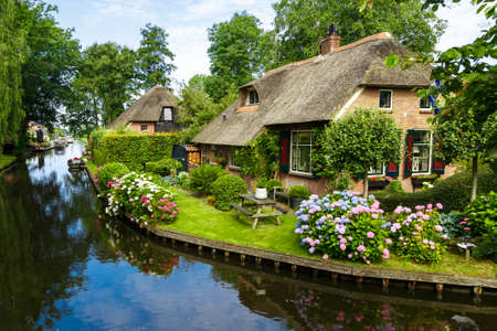 Landscape view of famous Giethoorn village with canals and rustic thatched roof houses in farm area. Banque d'images