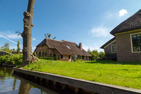 Landscape view of thatched rustic roof houses around canals in famous village Giethoorn.
