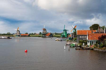 zaandam: ZAANDAM, NETHERLANDS - JULY 4, 2016 : View of famous windmills in Zaanse Schans village on cloudy sky. Zaandam is popular with windmills.