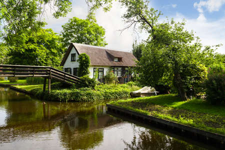 Landscape view of famous village of Giethoorn with small canals and thatched roof houses.