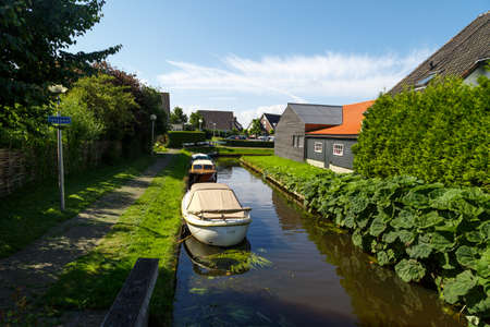 OVERIJSSEL, NETHERLANDS - JULY 4, 2016 : View of small sailboats in canals around trees in farm area. Giethoorn is very popular village. Editorial