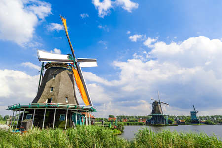 View of famous traditional windmills in Zaanse Schans village on cloudy sky background.