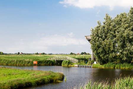 Landscape view of coastline of Zaanse Schans along river, on cloudy sky background.