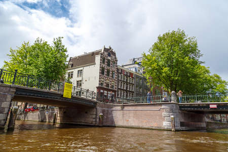 AMSTERDAM, NETHERLANDS - JULY 2, 2016 : View of architectural bridges on every canal, on cloudy sky. Amsterdam is popular with its canals.