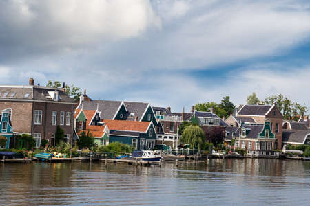 View of traditional small colorful village houses in farm area in Zaanse Schans, on cloudy sky background.