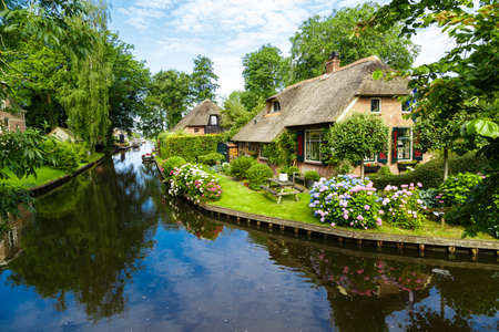 Landscape view of famous Giethoorn village with canals and rustic thatched roof houses in farm area. Stock Photo